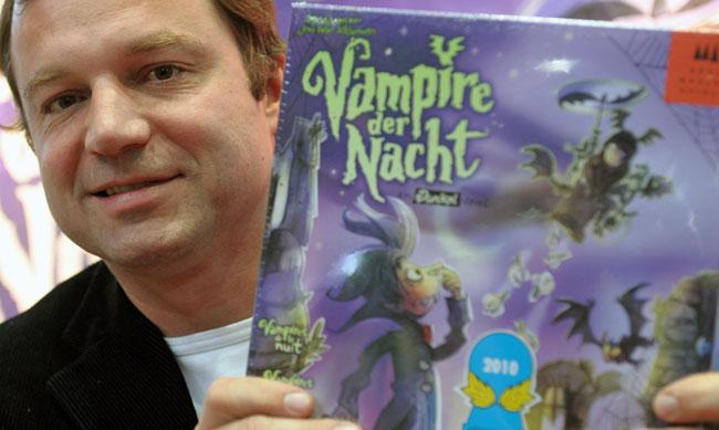 """Rolf Vogt, Gewinner des Graf Ludo 2010, Kinderspielgrafik, präsentiert das Spiel """"Vampire der Nacht"""" (Drei Magier Spiele). Foto: Leipziger Messe GmbH/Jens Schlüter"""
