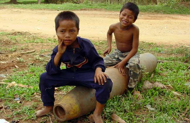Diese laotischen Kinder nutzen eine Bombenhülle als Spielzeug. Foto: T. West/Handicap International